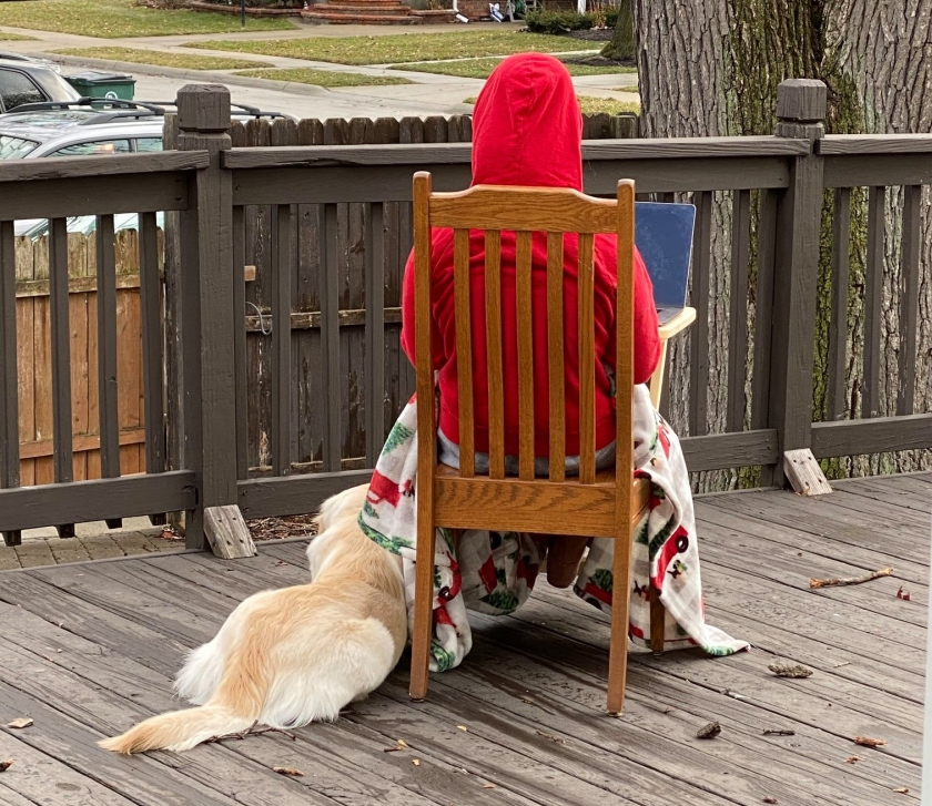 Sort of sad looking Cara wearing a red hoodie and sitting on her porch in a dining room chair, golden retriever dog at her feet.